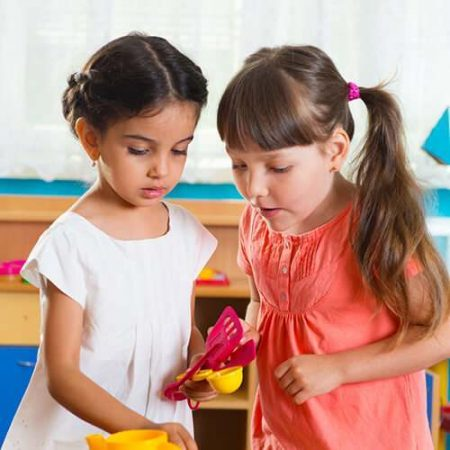 Two cute little girls playing with toys