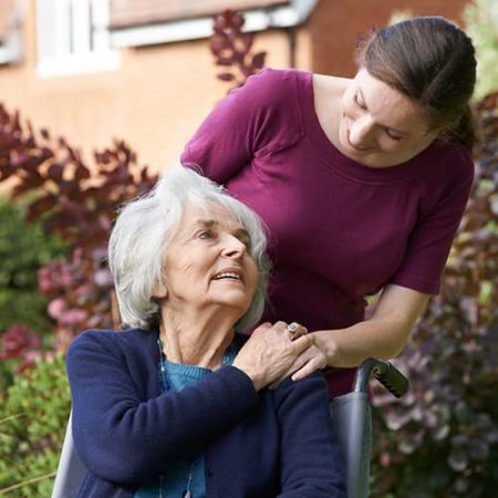 A homecare provider showing compassion to an aged woman