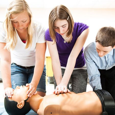 Students performing CPR on a dummy patient